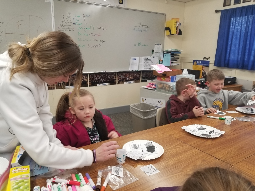 FFA member helping elementary students with her hands on activity